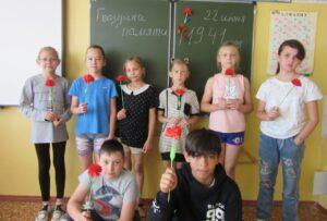 ребята стоят на фоне доски и в руках держат бумажные гвоздички