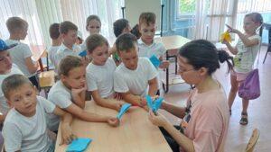 дети с педагогом делают птичек из бумаги